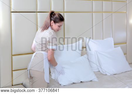 Maid Service In The Hotel Room. Cleaning Of Hotel Rooms. A Girl In Uniform Adjusts The Pillows On Th