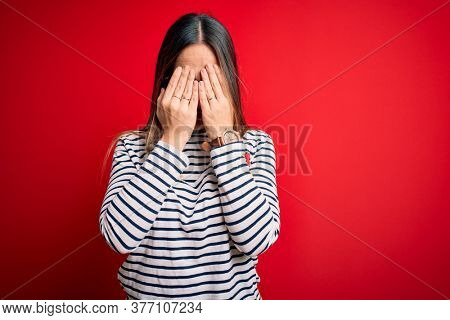 Young beautiful blonde woman with blue eyes wearing glasses standing over red background rubbing eyes for fatigue and headache, sleepy and tired expression. Vision problem