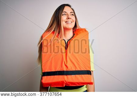 Young beautiful blonde woman with blue eyes wearing orange lifejacket over white background looking away to side with smile on face, natural expression. Laughing confident.