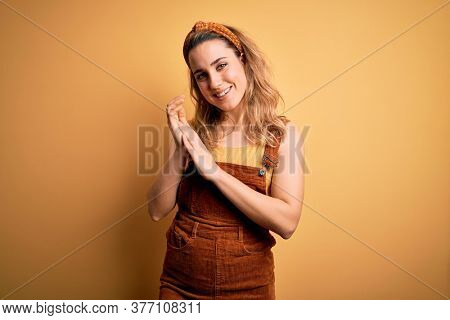 Young beautiful blonde woman wearing overalls and diadem standing over yellow background clapping and applauding happy and joyful, smiling proud hands together