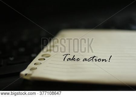 Motivational Text Message And Reminder - Take Action. Written On A Memo Notepaper With Blurry Black