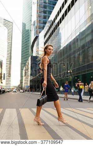 Full-length Portrait Of Slim Girl Walks On The Crosswalk, In Black Dress And White High Heels, Holdi