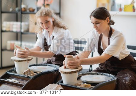Overview Of Two Young Potters By Pottery Wheels While Preparing Ceramic Pots From Raw Clay.