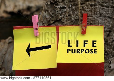 Life Purpose With A Direction Sign Message On Yellow Paper Notes Hanging On Wooden Wall. Find Your L