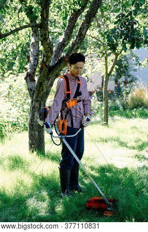 Female Gardener Mows The Grass In Garden Using String Trimmer. Garden Work Concept.