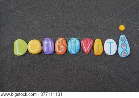 Longevity, Long Life Word Composed With Multicolored Stone Letters Over Black Volcanic Sand