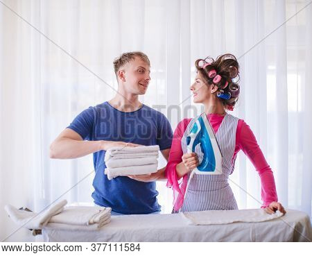 Young Couple At Home Doing Household Chores And Ironing. Wife Ironing Clothes For Her Husband At Wor
