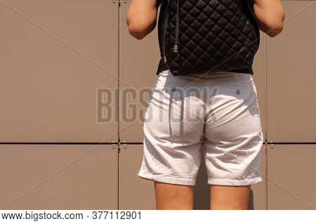 Back View Of Girl Showing Her Butt In Tight White Shorts On Bright Brown Background.