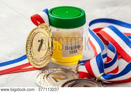 Doping Test. Gold, Silver And Bronze Medal And A Jar For Urine Analysis On A Gray Background