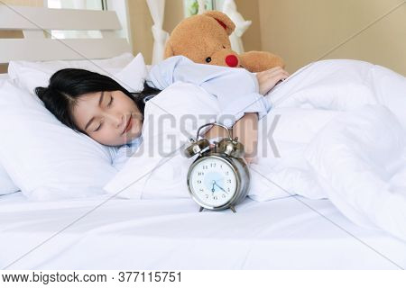 Portrait Young Woman On Pillow With Teddy Bear Sleeping Rest On The White Bed With Handles The Alarm