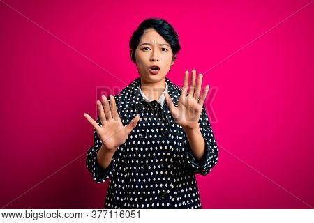 Young beautiful asian girl wearing casual jacket standing over isolated pink background Moving away hands palms showing refusal and denial with afraid and disgusting expression. Stop and forbidden.