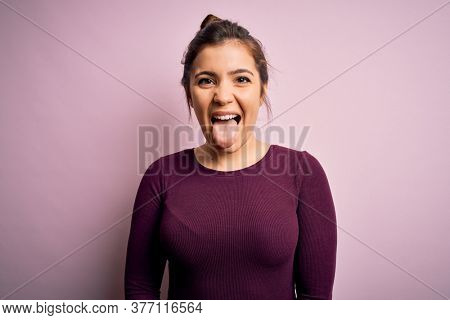 Beautiful young woman wearing casual bun hairstyle over pink isolated background sticking tongue out happy with funny expression. Emotion concept.
