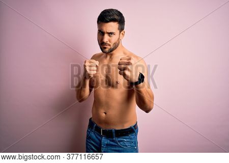 Young handsome strong man with beard shirtless standing over isolated pink background Punching fist to fight, aggressive and angry attack, threat and violence