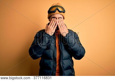 Young handsome skier man with beard wearing snow sportswear and ski goggles rubbing eyes for fatigue and headache, sleepy and tired expression. Vision problem