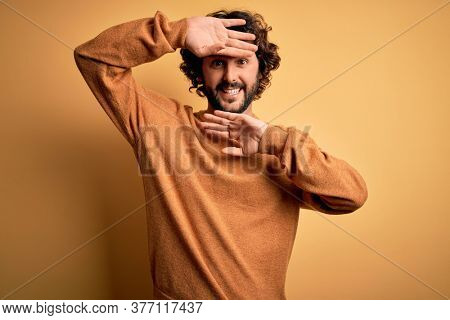 Young handsome man with beard wearing casual sweater standing over yellow background Smiling cheerful playing peek a boo with hands showing face. Surprised and exited