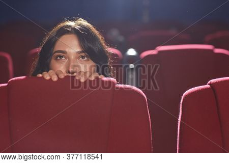 Portrait Of Scared Young Woman Hiding Behind Seat While Watching Horror Movie In Empty Cinema Hall,