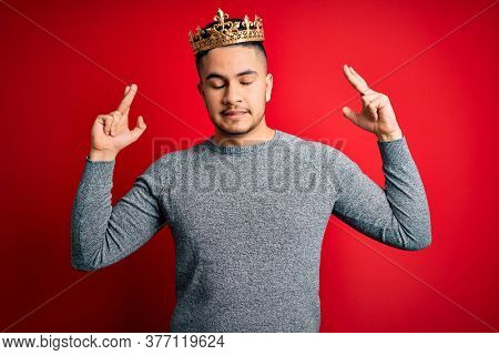 Young handsome man wearing golden crown of prince over isolated red background gesturing finger crossed smiling with hope and eyes closed. Luck and superstitious concept.
