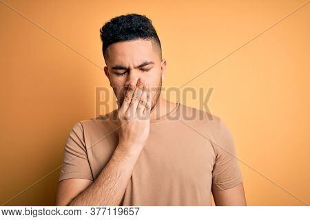 Young handsome man wearing casual t-shirt standing over isolated yellow background bored yawning tired covering mouth with hand. Restless and sleepiness.