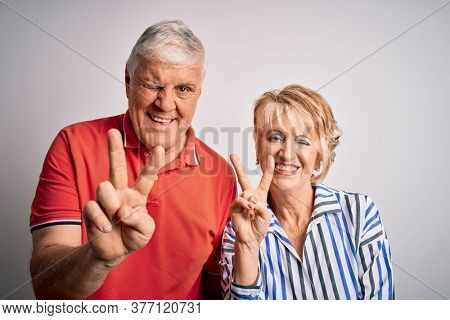 Senior beautiful couple standing together over isolated white background smiling with happy face winking at the camera doing victory sign with fingers. Number two.