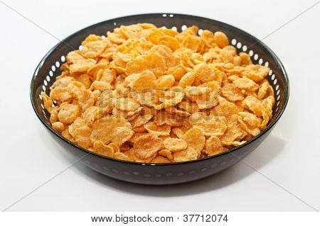 Golden Corn Flakes In Bowl Isolated On White