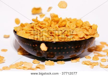 Golden Cornflakes Falling In A Bowl Isolated On White