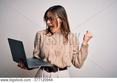 Young beautiful brunette woman working using laptop over isolated white background screaming proud and celebrating victory and success very excited, cheering emotion