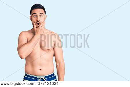 Young handsome man wearing swimwear looking fascinated with disbelief, surprise and amazed expression with hands on chin