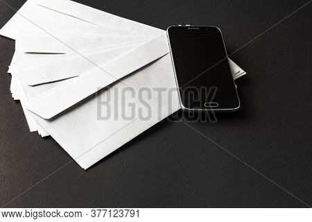 Black Office Desk Table With Smartphone With Blank Screen On Top Of Mail Envelopes Top View Business
