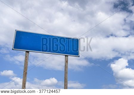 An Empty Billboard Or Road Sign Against A Blue Cloudy Sky. Mockup