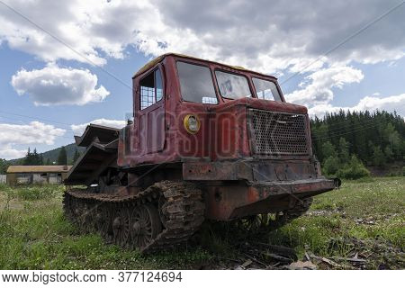 An Old Logging Truck, Rusty And Abandoned In A Field Against The Backdrop Of A Beautiful Forest, As