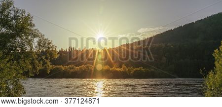 Sunset On The River. Reflection Of The Yellow Sun In The Water. Beautiful Siberian Landscape In The