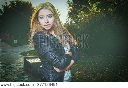 Sad Blonde Posing In Autumnal Park Backlit.