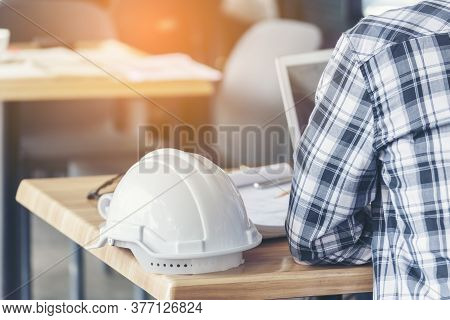 Civil Construction Engineer Working With Laptop At Desk Office With White Yellow Safety Hard Hat At