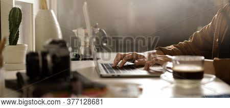 Female Photographer Holding Coffee Cup While Sitting At Worktable With Camera And Supplies In Studio