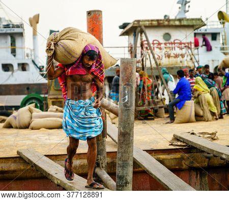 Chittagong, Bangladesh, December 22, 2017: Manual offloading of cargo from ships at the Karnaphuli River port in Chittagong, Bangladesh