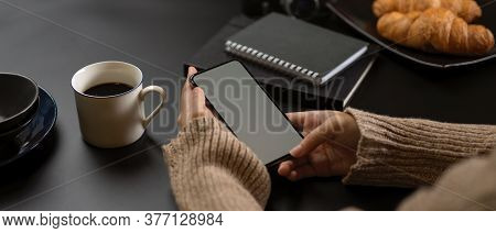Female Take A Break With Mock Up Smartphone While Sitting At Workspace With Supplies, Coffee Cup And