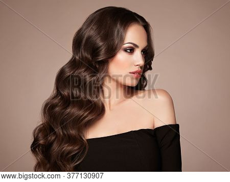 Brunette Girl With Long Healthy And Shiny Curly Hair. Care And Beauty. Beautiful Model Woman With Wa