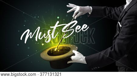 Magician is showing magic trick with Must See inscription, traveling concept
