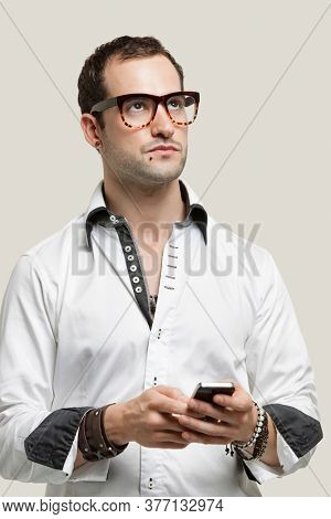 Young man using cell phone for text messaging against gray background