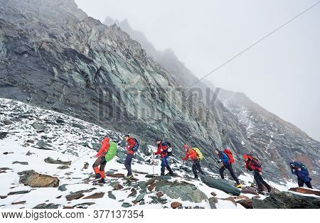 Side View Of Hikers Team With Backpacks, Trekking Sticks Walking On Rocky Path At The Bottom Of Moun