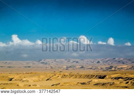 Desert in Egypt. Rocky sand hills. A lone tourist on an ATV in the desert against the background of blue sky and mountains is walking towards the Red Sea. Landscape in the desert.