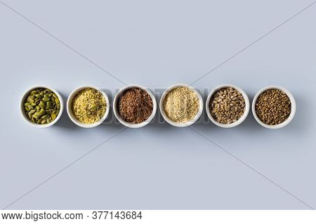Different Seeds - Hemp, Sesame, Sunflowers Seeds And Pumpkin Seeds In Small Bowl Top View On Blue Ba