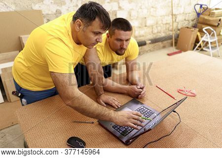 Two Carpenters In Yellow T-shirts Using Laptop While Discussing Furniture In Workshop While Working