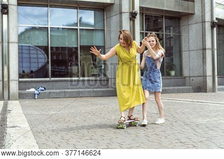 Young Mother Practising On Skateboard In The City Street. Daughter Helping Mum On Skateboard. Mum Le