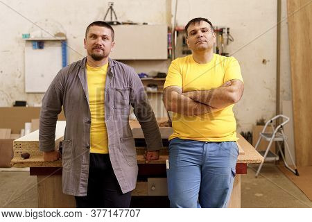 Smiling Confident Carpenters Near Their Workbench In Their Workshop Looking To Camera