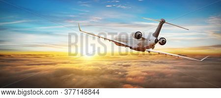 Private jetplane flying above clouds, backside view. Sunset light