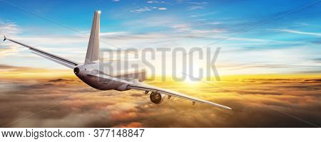 Commercial airplane flying above clouds, backside view. Sunset light