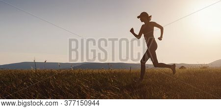 Jogging Woman Running In Summer Field At Sunset