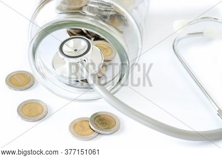 Stethoscope On Bottle And Coin On White Background. Concept For Finance Health Check Or Cost Of Busi