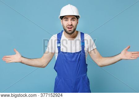 Perplexed Puzzled Young Man In Coveralls Protective Helmet Hardhat Isolated On Pastel Blue Wall Back